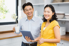 Happy expectant couple using tablet Stock Image