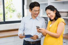 Happy expectant couple using tablet and smartphone Stock Photos