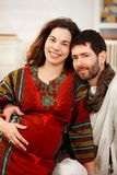 Happy expectant couple in nursery. Happy expectant couple wearing arabic style clothes, husband listening baby Royalty Free Stock Photography