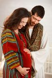 Happy expectant couple in nursery. Happy expectant couple wearing arabic style clothes, husband listening baby Royalty Free Stock Images