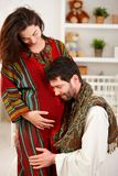 Happy expectant couple in nursery. Happy expectant couple wearing arabic style clothes, husband listening baby Stock Photos