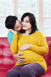 Happy expectant mother kissed by her husband Stock Photography