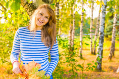 Happy expectant mother walks in park. Happy expectant mother walks in autumn park royalty free stock image