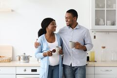 Free Happy Expecting Black Family Drinking Coffee In Kitchen Stock Photo - 213876930