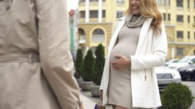 Happy expecting mother stroking abdomen, talking to friend city street, advise stock photo
