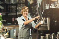 Experienced barista making coffee in professional coffee machine. Happy experienced barista making coffee in professional coffee machine. Woman preparing stock image