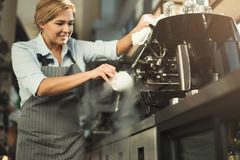 Experienced barista making coffee in professional coffee machine. Happy experienced barista in uniform making coffee in professional coffee machine. Woman royalty free stock images