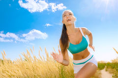 Happy expressive young woman running outdoors Stock Images