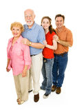 Happy Extended Family. Grandparents, middle aged father, and teen girl, all together.  Full body isolated on white Royalty Free Stock Photography
