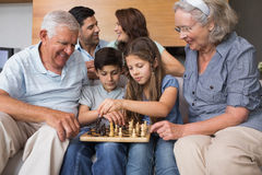 Happy extended family playing chess in the living room Royalty Free Stock Photo