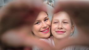 Happy face of attractive young mother kissing cute teen daughter making heart gesture by hand. Looking at camera. Smiling family woman and kid girl posing stock footage