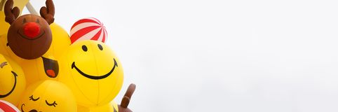 Happy face balloons. A soft focus on the yellow balloon with smiling face from worm eye view. Long website banner with copy space. On the right space for your royalty free stock photos