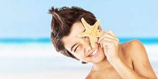 Happy face boy with starfish on the beach. Happy face cute boy with starfish on the beach, closeup portrait of preteen brunette child, male kid model having fun royalty free stock images
