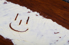A happy face drawed in stevia powder on wooden background Stock Photo