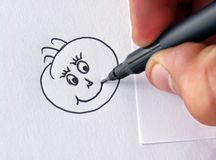 Happy face drawing. Hand and pen drawing a smiley happy face on paper Stock Images