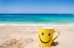 Happy face mug on the beach Stock Images