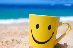 Happy face mug on the beach Stock Photo