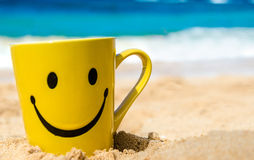 Happy face mug on the beach Royalty Free Stock Photography