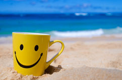 Happy face mug on the beach Stock Image