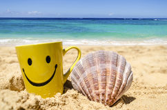 Happy face mug on the beach with seashell Royalty Free Stock Photos