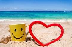 Happy face mug with heart shape on the beach Stock Photography