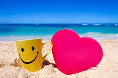 Happy face mug with heart shape on the beach
