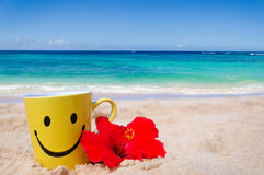 Happy face mug with red hibiscus on the beach Stock Photos