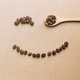 Happy face shaped of coffee beans with wooden spoon Royalty Free Stock Photos