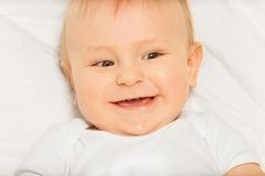 Happy face of small baby wearing white bodysuit stock image