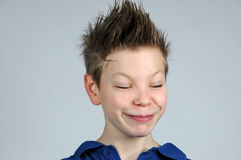 Happy face. Happy teenager boy  with punk hairstyle and closed eyes Stock Photos