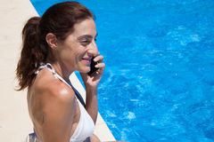 Happy face woman talking on the phone on curb pool Royalty Free Stock Photo