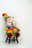 Happy faced clown doll sitting on a time out chair. Happy faced clown doll sitting on a time-out chair with blue yellow, green, orange clothing and hat with a stock photo