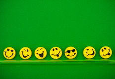 Happy Faces. Row of happy faces on green background, happy faces Stock Photo