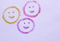 Happy faces on a white background. Three smiley faces painted on a white background Stock Images