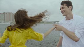 Smiling girl and jolly boy dance some folk dance on rain pools of a pier stock footage
