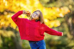 Happy fall girl smiling and joyful holding autumn leaves. Beautiful young girl with maple leaves in red cardigan royalty free stock images