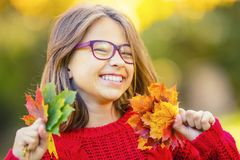 Happy fall girl smiling and joyful holding autumn leaves. Beautiful young girl with maple leaves in red cardigan stock photo