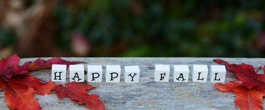 HAPPY FALL letter blocks on Autumn background Royalty Free Stock Photography