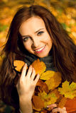 Happy fall woman smiling joyful and blissful holding autumn leaves Stock Photos