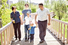 Happy famHappy family spending time outdoors on a Sunny summer day. mom, dad ,grandma and two boys. Happy family spending time outdoors on a Sunny summer day stock photo