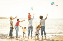 Happy families group with parents and children playing with kite at beach. Vacation - Summer joy happiness concept with mixed race people having fun together at Stock Images