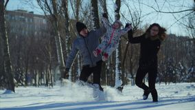 4K Happy familly runs in the park. Mother and father hold the child and lift him up stock footage