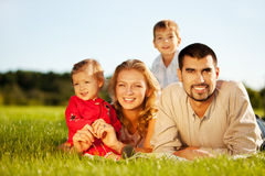 Happy family. Of 4 people lying ona grass under summer sun. Focus is on the man Royalty Free Stock Photography