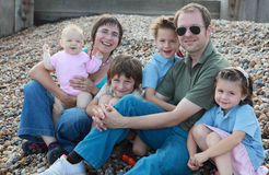 Happy family. Portrait of happy family of six sitting on the beach Royalty Free Stock Image