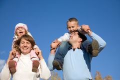 Happy family. Happy parents hold on shoulders of beautiful small children against the blue sky Stock Image