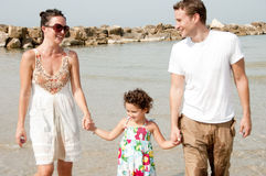 Happy family. Young couple embracing and enjoying with young daughter in the beach stock photo