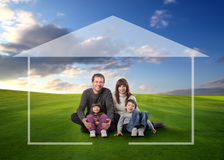 Happy family. Seated in a grass field and surrounded by home drawing Royalty Free Stock Images