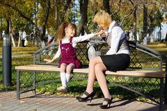 Happy mother and daughter in autumn city park Stock Images