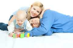 Happy family. Home: father, mother and baby lying down and smiling royalty free stock photos