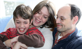A Happy Family. A smiling mother hugs her laughing son as father looks on Stock Photography